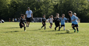 Children playing soccer on a field with their coach.