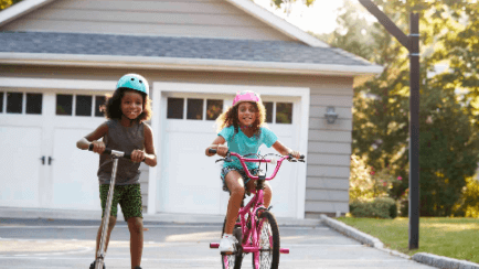Two girls in front of a house garage riding a bicycle and a scooter.